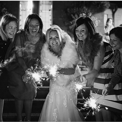 A group of ladies with sparklers around the bride, in black and white