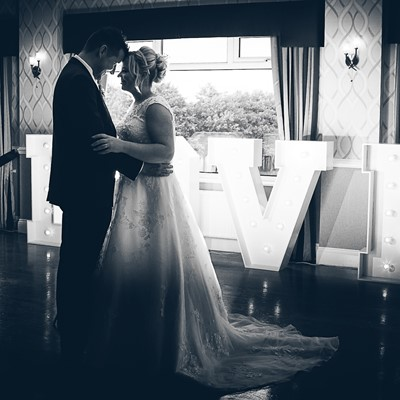 Bride & groom on dancefloor with Love letters behind in black and white
