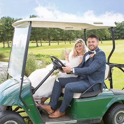 A couple sat on a golf buggy with lush green trees behind them.