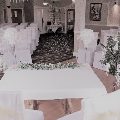 The room set up for a civil ceremony wedding taken looking from the head table